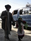 Afghanistan - Kunduz / Kondoz: a blind man is led by a child - photo by J.Marian