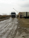Astara, Azerbaijan: Azeri-Iranian border - main vehicle border crossing - a muddy and litter strewn track alongside the beach - Mercedes-Benz truck clears customs - photo by F.MacLachlan