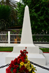 Douala,Cameroon: white obelisk - tomb with flowers downtown, by the gardens of the Chamber of Commerce - photo by M.Torres