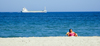 La Pineda, Vila-seca, Costa Dorada, Tarragona, Catalonia: woman on a deck chair and a passing freighter - photo by B.Henry