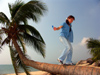 China - Hainan Island: gril walking on a coconut tree (photo by G.Friedman)