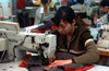 Dongguan, Guangdong province, China: seamstress using a sewing machine - Chinese factory worker - photo by B.Henry