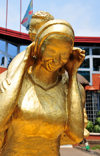Goma, Nord-Kivu, Democratic Republic of the Congo: gilded statue of an African woman with a baby on her back - grin - Hotel Vip Palace in the background, Blvd Kanyamuhanga - photo by M.Torres