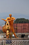 Goma, Nord-Kivu, Democratic Republic of the Congo: gilded statue of a cargo bike and its pusher, carrying the globe - roundabout center celebrating 50 years of Congolese independence - local trottinette called a chuckadoo, the symbol of Goma - photo by M.Torres