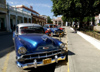 Cuba - Holguín - blue cars parked along curb - photo by G.Friedman