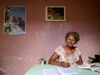 Cuba - Holguín - secretary and red wall - an office worker studies at her desk - photo by G.Friedman