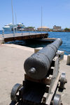 Curacao - Willemstad: Old Cannon in front of Koninin Emma Brug (pontoon bridge)with cruise ship moored off Otrobanda Mega Pier in the background - photo by S.Green
