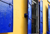 Puerto Plata, Dominican republic: yellow wall and windows with blue shutters - photo by M.Torres
