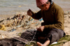 Egypt - Alexandria: fisherman mending nets (photo by John Wreford)