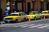San Salvador, El Salvador, Central America: Parque Libertad - yellow taxis with black and white checker stripes along 'los portales' - photo by M.Torres