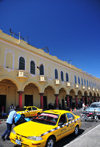San Salvador, El Salvador, Central America: Parque Libertad - arcade and yellow taxis - 'los portales' - photo by M.Torres
