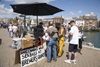 Weymouth, Dorset, England: people buying fresh line caught sea bass off local man in Brewers Quay - photo by I.Middleton