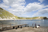 Lulworth Cove, Dorset, England: men dragging boat up beach - photo by I.Middleton