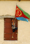 Eritrea - Hagaz / Agaz, Anseba region - boy placing the flag of Eritrea on a house - photo by E.Petitalot
