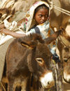 Eritrea - Senafe, Southern region: girl unloading her donkeys at the market - photo by E.Petitalot