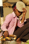 Eritrea - Mendefera, Southern region: a girl selling roasted corn cobs at the market - photo by E.Petitalot