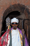Lalibela, Amhara region, Ethiopia: Bet Mikael church - Coptic priest with cross and mequamia praying stick - photo by M.Torres