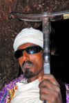 Lalibela, Amhara region, Ethiopia: Bet Mikael church - Coptic priest with mequamia praying stick - photo by M.Torres
