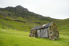 Trøllanes, Kalsoy island, Norðoyar, Faroes: rural cottage under a towering basalt peak - photo by A.Ferrari