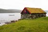 S�rvagsvatn lake, V�gar island, Faroes: small stone house with sod roof on the lake shore - torvtak - photo by A.Ferrari