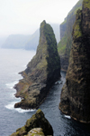 V�gar island, Faroes: Geituskorardrangur - a towering basalt stack standing 116m above the ocean, by the vertical cliff face - photo by A.Ferrari
