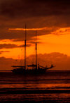 Yasawa Islands, Fiji: orange sunset with cloud cover over the Pacific Ocean – silhouette of La Violante, a 1920s double-masted schooner - photo by C.Lovell