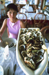 Sète, Hérault, Languedoc-Roussillon, France: a generous serving of oysters - young lady in a restaurant - photo by K.Gapys