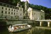 Brantôme / Brantòsme, Dordogne, Aquitaine, France: tour boat on theriver Dronne next to the Benedictine Abbey of Brantôme - founded in 769 by Charlemagne - the Romanesque bell-tower it the oldest in France - photo by K.Gapys