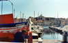 France - Marseilles (Bouches-du-Rhone / PACA): sailor in the habour - church in the background (photo by G.Frysinger)