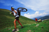 Chamonix, Haute-Savoi, Rh�ne-Alpes, France: a mountainbiker carrying his bike on the trail while other negotiates passage with a sheep - photo by S.Egeberg