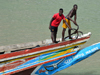 Barra, The Gambia: Gambian sailors - fishermen preparing the anchor on the bow of a traditional wooden fishing boat - River Gambia estuary - photo by M.Torres