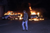 Germany - Berlin: riots on May 1st - pedestrian passes burning cars - photo by W.Schmidt