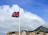 Gibraltar: Union Jack in the wind and southern view of the Rock, Europa Point - orographic clouds - hoto by M.Torres