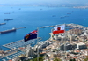 Gibraltar: flag of Gibraltar (right) and the Government Ensign (left) - seen against the bay of Algeciras and the town - photo by M.Torres