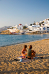 Greek islands - Mykonos (Hora) / Mikonos / JMK: town beach - two girls sitting - photo by D.Simth