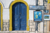 Greece, Kastellorizo: brightlypainted wooden door and signs on a harbourside building - photo by P.Hellander