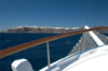Greece, Cyclades, Santorini: view of distant Oia on the cliff edges from a cruise caique at sea - photo by P.Hellander