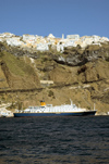 Greece, Cyclades, Santorini: view of Fira on the clifftops while a small cruise ship lies at anchorin the caldera - photo by P.Hellander