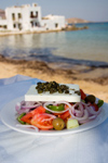Greece - Paros: Greek Salad in table in foreground with background Naousa beach - photo by D.Smith