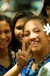 Hawai'i - Oahu island - Waikiki beach: teenage girls dressed in Hula costume with one girl showing peace symbol and wearing a flower in her hair - photo by D.Smith