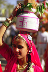 India - Rajasthan: Rashput woman with her typical jewels and clothes with a pot of water on her head - photo by E.Petitalot