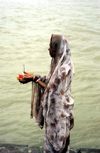 India - Uttaranchal - Rishikesh: a pilgrim prepares to place an offering on the Ganges / Ganga river - photo by W.Allgöwer
