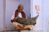 Pushkar, Rajasthan, India: man reading a newspaper - photo by M.Wright