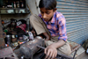 Calcutta / Kolkata, West Bengal, India: child working with metal in the streets - child labour - photo by G.Koelman