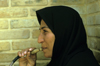 Iran - Shiraz, Fars province: woman with chador smoking a water pipe - narghile - photo by W.Allgower