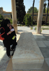 Iran - Shiraz: Mausoleum of Hafez - a woman read as poem by the Hafez's alabaster tombstone - photo by M.Torres