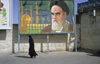 Iran - Qom: woman under billboard with Ayatollah Ruhollah Khomeini - photo by W.Allgower