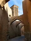 Yazd, Iran: a quintessential alley of Yazd, with pointed arches and a wind catcher - old town - photo by N.Mahmudova