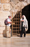 Jerusalem,  Israel: secular man with a backpack and an Orthodox Jew covered in a Kosher wool Tallit prayer shawl - Western Wall plaza - photo by M.Torres