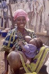 C�te d'Ivoire - Smiling lady and her baby - breast feeding outdoors (photo by J.Filshie)